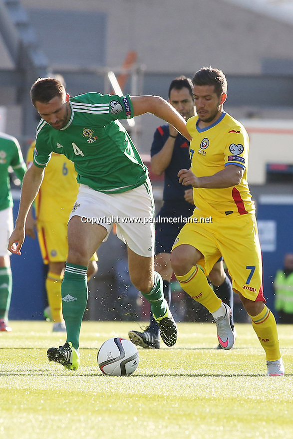 Romania's Alexandru Chipciu is blocked by Northern Ireland's 4 Gareth McAuley during the UEFA EURO 2016 qualifying Group F soccer match between Northern Ireland and Romania at Windsor Park in Belfast, Northern Ireland, 13 June 2015.  EPA/PauL McErlane