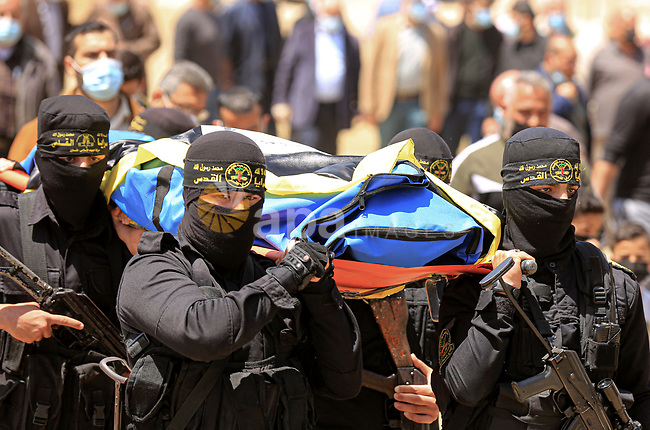 Members of Islamic Jihad movement attend the funeral of senior leader of Islamic Jihad Ahmed Abu Hasera,  who died of the coronavirus (COVID-19) pandemic in Gaza City on April 25, 2021. Minister of Health Mai Alkaila said today that 714 new COVID-19 infections, 16 deaths and 1952 recoveries were registered in Palestine during the past 24 hours. Alkaila said seven deaths were reported in the West Bank and nine others in the Gaza Strip. In the West Bank, 409 coronavirus tests came out positive, while 305 new cases were registered in the Gaza Strip. Photo by Dawoud abo alkas