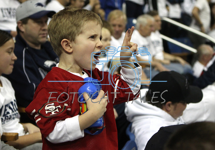 """Zachary Folen, 4, show his support for quarterback Colin Kaepernick by """"Kaepernicking"""" during the NCAA men's basketball game between San Diego State and Nevada, on Wednesday, Jan. 23, 2013 in Reno, Nev. Nevada officials held a 15-second event encouraging fans to kiss their biceps in honor of Kaepernick who graduated from Nevada in 2011. (AP Photo/Cathleen Allison)"""
