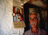 Rio de Janeiro State, Brazil. Old man from the Interior with a picture of Christ on an old calendar. His skin has the same old wrinkled texture as thecracked  white washed wall.