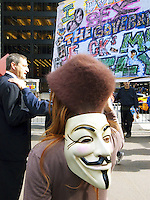 """USA. New York City. Occupy Wall Street (OWS) is a people-powered movement that began on September 17, 2011 in Liberty Square in the Wall Street financial district of Manhattan. The protesters have created a small campsite at the Zuccotti Park site. OWS and has spread to over 100 cities in the United States and actions in over 1,500 cities globally. OWS is mainly protesting social and economic inequality, corporate greed, corruption and influence over government—particularly from the financial services sector—and lobbyists.  It is fighting back against the corrosive power of major banks and multinational corporations over the democratic process, and the role of Wall Street in creating an economic collapse that has caused the greatest recession in generations. The protesters' slogan, """"We are the 99%"""", refers to the difference in wealth and income growth in the U.S. between the wealthiest 1% and the rest of the population. OWS aims to expose how the richest 1% of people are writing the rules of an unfair global economy that is foreclosing on our future. OWS has being organized using a non-binding consensus based collective decision making tool known as a """"people's assembly"""". A woman with the Guy Fawkes mask on the back of her head. The Guy Fawkes mask is the face of a dead man, the visage of Vendetta, in comic books and a popular Hollywood film; but mostly the avatar of Anonymous, the group of hacktivists who are legion online; and the image worn by Occupy Wall Street activists. 20.10.2011 © 2011 Didier Ruef"""