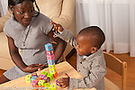 2 year old toddler boy bulding block tower with mother encouraging him nearby