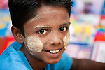 Portrait of a boy with the traditional face make-up and sun screen thanakha, Myanmar