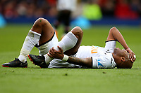 Andre Ayew of Swansea City lies injured on the pitch during the Premier League match between Manchester United and Swansea City at the Old Trafford, Manchester, England, UK. Saturday 31 March 2018