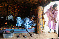 BURKINA FASO Djibo, malian refugees, mostly Touaregs, in refugee camp Mentao of UNHCR, they fled due to war and islamist terror in Northern Mali , Tuareg master from Tombouctou instruct his black african servant /BURKINA FASO Djibo , malische Fluechtlinge, vorwiegend Tuaregs, im Fluechtlingslager Mentao des UN Hilfswerks UNHCR, sie sind vor dem Krieg und islamistischem Terror aus ihrer Heimat in Nordmali geflohen, Tuareg Mann aus Timbuktu instruiert seinen schwarzafrikanischen Diener