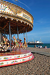 Great Britain, England, East Sussex, Brighton: Carousel on Brighton beach with Brighton Pier behind