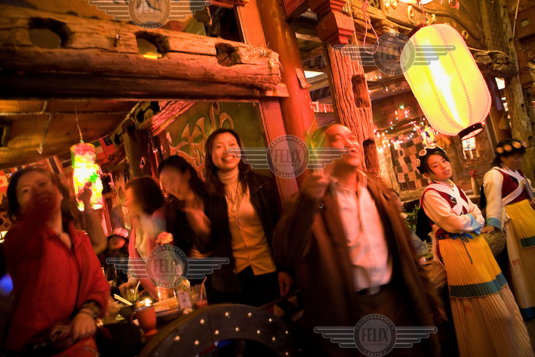 Tourists sing in a bar while Nakhi (Naxi) girls in traditional costume wait for potential clientele in the old city of Lijiang, a centre of Nakhi culture which is a UNESCO World Heritage Site.