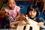 Education preschool 3-4 year olds boy and girl playing with human figures and dollhouse talking and moving them around