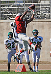 Football action. Wide receiver goes up high to make the catch.