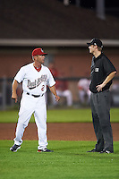 Auburn Doubledays hitting coach Mark Harris (2) argues a call with umpire Louie Krupa during a game against the Tri-City ValleyCats on August 25, 2016 at Falcon Park in Auburn, New York.  Tri-City defeated Auburn 4-3.  (Mike Janes/Four Seam Images)