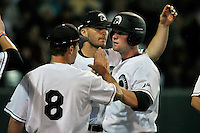 First baseman Jake Beaver (11) of the USC Upstate Spartans is congratulated by teammate Pat Raiff (8) after scoring a run in a game against the South Carolina Gamecocks on Tuesday, March 15, 2016, at Fluor Field at the West End in Greenville, South Carolina. (Tom Priddy/Four Seam Images)