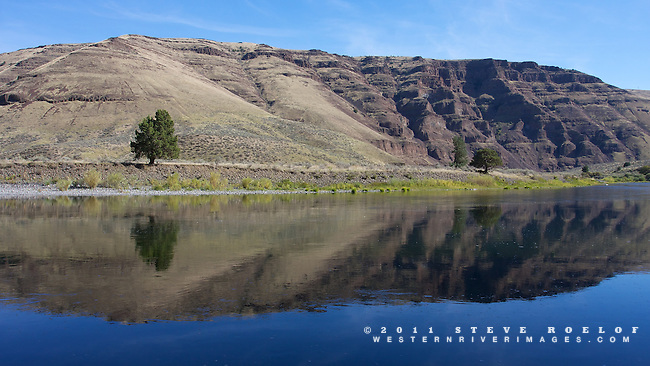 A blue sky reflects in the John Day River, Oregon.