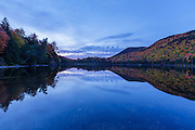 Reflection of autumn foliage in Upper Hall Pond in Sandwich, New Hampshire USA on a cloudy day during morning blue hour.