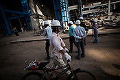 A Chinese engineer from Sepco cycles past at the construction site of the Adani Power plant of 4620 MW capacity in Mundra port industrial city of Gujarat, India. Indian power companies have handed out dozens of major contracts to Chinese firms since 2008. Adani Power Ltd have built elaborate Chinatowns to accommodate Chinese workers, complete with Chinese chefs, ping pong tables and Chinese television. Chinese companies now supply equipment for about 25% of the 80,000 megawatts in new capacity.