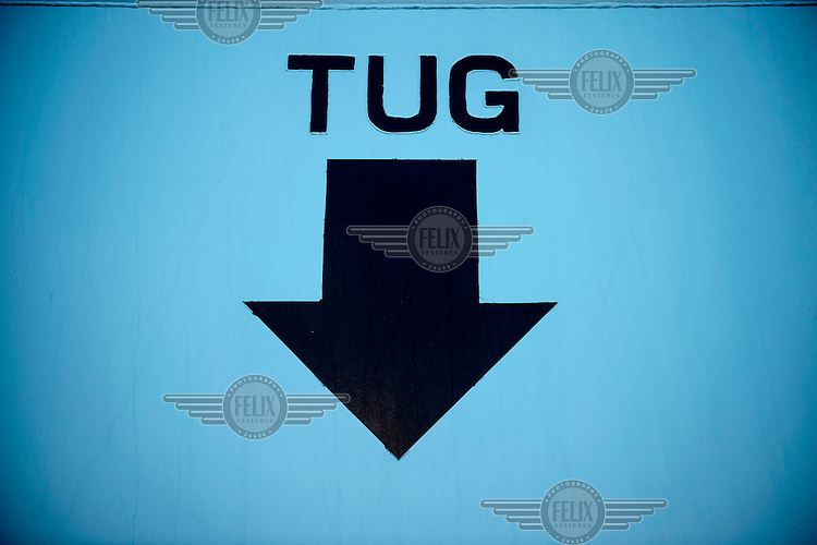 A sign on the side of the Mary Maersk, the largest container ship in the world, showing tugs where to position themselves when helping to steer the ship.