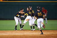 Bradenton Marauders Kevin Kramer (14) starting to get mobbed by teammates, including Wyatt Mathisen (28), Tomas Morales (27) and Jordan Luplow (26), after a walk off hit during a game against the Palm Beach Cardinals on August 8, 2016 at McKechnie Field in Bradenton, Florida.  Bradenton defeated Palm Beach 5-4.  (Mike Janes/Four Seam Images)