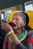 "Kayapo Chief Raoni Txucarrhamae smokes his pipe, with headress and ""Rio+20"" yellow wrist band for participants. The People's Summit at the United Nations Conference on Sustainable Development, Rio de Janeiro, Brazil."