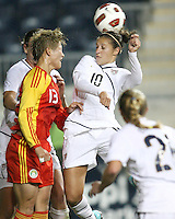 Carli Lloyd #10 of the USA WNT heads past Jun Ma #13 of the PRC WNT during an international friendly match at PPL Park, on October 6 2010 in Chester, PA. The game ended in a 1-1 tie.