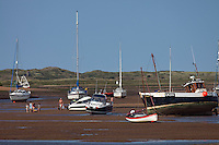 Brancaster Staithe, Norfolk, England, 09/08/2009..Holidaymakers cross the creeks at low tide.