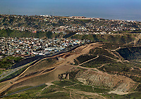 aerial photograph of the United States Mexico border near the Pacific Ocean, San Diego County, California.  A portion of Tijuana, Mexico is at the right.