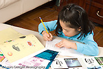 8 year old girl at home doing homework for Chinese language class