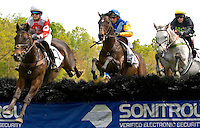 Jockey's make a jump during the Queen's Cup Steeplechase in Mineral Springs, NC.