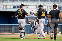 FCL Pirates Black catcher Henry Davis (32) fist bumps starting pitcher Cristopher Cruz (30) after the bottom of the first inning during a game against the FCL Rays on August 3, 2021 at Charlotte Sports Park in Port Charlotte, Florida.  Davis was making his professional debut after being selected first overall in the MLB Draft out of Louisville by the Pittsburgh Pirates.  (Mike Janes/Four Seam Images)