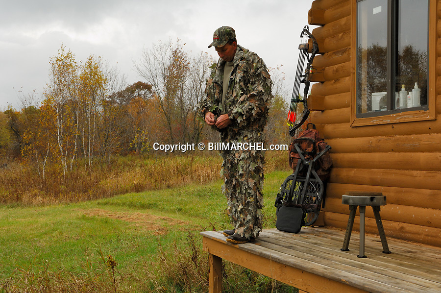 00105-042.10 Bowhunting (DIGITAL) Archer is preparing to hunt while on porch of hunting shack.  Backpack, tree stand.  H3L1