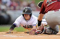 Shortstop Hunter Burton (1) of the Furman Paladins is out at home trying to advance on a hit as catcher Grayson Greiner (21) of the South Carolina Gamecocks applies the tag to end the first inning in a game on Tuesday, April 8, 2014, at Fluor Field at the West End in Greenville, South Carolina. South Carolina won, 9-2. (Tom Priddy/Four Seam Images)