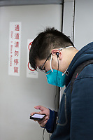 A man reads the news on his cellphone during the morning commute on the Beijing subway. Many residents now not only wear the masks outdoors but also in indoor public spaces and on public transportation. PM2.5 reading - 93 - Moderate