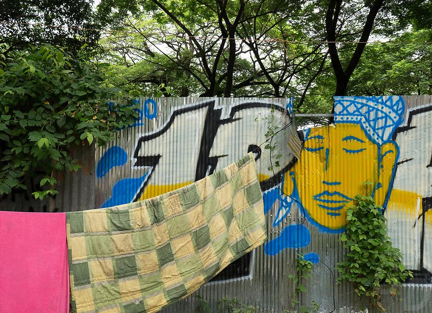Graffiti and washing on a corrugated iron fence along the road to Angkor Wat, Cambodia