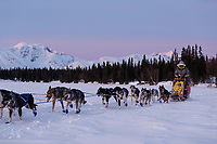 Wade Marrs runs on Finger Lake with the Alaska Range in the background at sunrise in the morning at Finger Lake checkpoint during the 2019 Iditarod on Monday March 4, 2019<br /> <br /> Photo by Jeff Schultz/  (C) 2019  ALL RIGHTS RESERVED