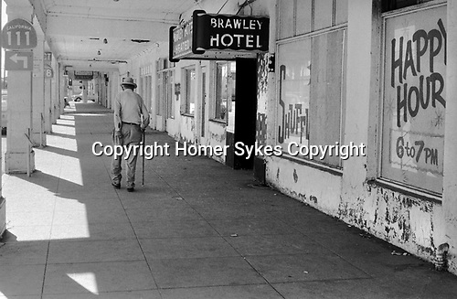 Senior man scratching his bottom urban poverty outside of the cheap and run down Brawley Hotel advertising Happy Hour,  Brawley, New Mexico 1972 1970s USA