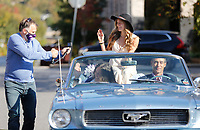 Trey Marley, communication projects manager with Fayetteville Public Schools, shoots video Friday, October 16, 2020 of MaryMargaret Harris, one of two Homecoming Queens at Fayetteville High School, as she rides in the back of a 1966 Ford Mustang with her parents  Amanda Harris and Chris Harris on the square in Fayetteville. The school district is making a video of the homecoming court for  viewing at the October 23rd football game. The school is not having it's annual homecoming parade or homecoming dance because of the covid-19 pandemic. Victoria Bogomilova is the other queen because of a tie in the voting. Check out nwaonline.com/201017Daily/ and nwadg.com/photos for a photo gallery.(NWA Democrat-Gazette/David Gottschalk)