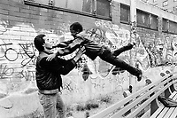 """USA. New York City. Spanish Harlem. Carlos (L) and his brother Willie (R) are both Puerto Rican adolescents. They play together outside. The family lives below the poverty line and receives public assistance (AFDC, Home Relief, Supplemental Security Income and Medicaid). The family resides in units managed by the New York City Housing Authority (NYCHA) which provides housing for low income residents. NYCHA administers rental apartments in facilities, popularly known as """"projects"""". Spanish Harlem, also known as El Barrio and East Harlem, is a low income neighborhood in Harlem area. Spanish Harlem is one of the largest predominantly Latino communities in New York City. 10.05.86 © 1986 Didier Ruef"""