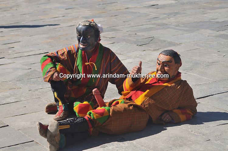 """Two clowns perfom during annual Thimpu Tshechu. The Tshechu is a festival honouring Guru Padmasambhava, """"one who was born from a lotus flower."""" This Indian saint contributed enormously to the diffusion of Tantric Buddhism in the Himalayan regions of Tibet, Nepal, Bhutan etc. around 800 AD. He is the founder of the Nyingmapa, the """"old school"""" of Lamaism which still has numerous followers. The biography of Guru is highlighted by 12 episodes of the model of the Buddha Shakyamuni's life. Each episode is commemorated around the year on the 10th day of the month by """"the Tschechu"""". The dates and the duration of the festivals vary from one district to another but they always take place on or around the 10th day of the month according to the Bhutanese calendar. During Tshechus, the dances are performed by monks as well as by laymen. The Tshechu is a religious festival and by attending it, it is believed one gains merits. It is also a yearly social gathering where the people, dressed in all their finery, come together to rejoice. Arindam Mukherjee."""