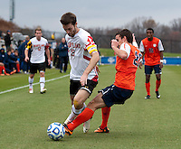 Patrick Mullins (15) of Maryland has the ball tackled away from him by Patrick Foss (20) of Virginia during the ACC Finals at the Maryland SoccerPlex in Boyds, MD.  Maryland defeated Virginia, 1-0, to win the title.