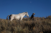 Edgar Oscanoa leads Dot through tall grasses to be saddled.  He tends sheep in Upper Gully in southern Wyoming. Peruvian shepherds traditionally work at the ranch watching over sheep.  Dot, an adopted mustang that came from the correctional center in Riverside, saved a shepherd's life by finding his way home on a cold night when they were lost.  Nelson, the saved worker, left years ago but the horse is still a favorite among ranch hands like Edgar.