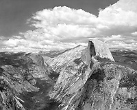 """""""Clouds Over Half Dome"""" <br /> Yosemite National Park, California<br /> <br /> The popular Glacier Point Overlook offers the most stupendous view of Yosemite Valley in the entire park. On this particular day, the sky was clear and I composed an image of Half Dome but decided not to expose the film after concluding that I had already seen that photo a thousand times. After sitting quietly to enjoy the view for an hour, a line of fast moving clouds headed my way. I quickly added an orange-red filter to clear the atmospheric haze substantially, darken the blue sky, enhance structure within the clouds and enhance the coarseness of the rocks. The line of clouds in the photograph visually reinforces the line of the valley walls. A large, high resolution print of this image does a good job of conveying the immensity of the scene through the small size of the very large trees on the valley floor."""