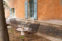 Prieure de St Jean de Bebian. Pezenas region. Languedoc. The villa. Window. Lounging chairs, garden furniture. In the garden. France. Europe.