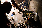 Two men cook a duck for dinner over an open fire in a wok. Lombok, Indonesia.