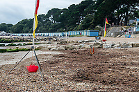 BNPS.co.uk (01202 558833)<br /> Pic: MaxWillcock/BNPS<br /> <br /> Pictured: The mass of rotten seaweed in between red and yellow flags on Avon Beach.<br /> <br /> A south coast beach has become a no-go zone at the height of the summer holidays after a mass of rotten seaweed was allowed to fester on the sand.<br /> <br /> The vast carpet of kelp has been left to gather on Avon Beach in Christchurch, Dorset, for over a month.<br /> <br /> The unpleasant mess is attracting flies and is putting people off visiting the beauty spot which is normally hugely popular with families.<br /> <br /> Bathers are having to wade through the sticky seaweed to get to the sea and are usually left with their legs covered in it.