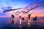 Fisherman with large nets reflects in water during sunrise by Bang Nguyen Trong