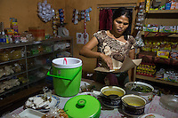 Bali, Indonesia.  Woman Making Breakfast Packets in her Home for Customers, Babakan Village.