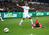 SWANSEA, WALES - MARCH 16: Wayne Routledge of Swansea (L) raises his hands in the air in protest to a push by Alberto Moreno (R) of Liverpool during the Premier League match between Swansea City and Liverpool at the Liberty Stadium on March 16, 2015 in Swansea, Wales