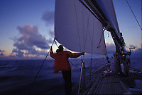 Man standing watch at sunrise aboard sailing yacht 'Heron', a Halberg-Rassy 46, in tropical waters with red jacket