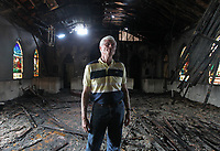 Pastor Kyle Clements stands inside the burned out sanctuary of the Ruckersville Baptist Church Monday in Ruckersville, Va. Arson is suspected as the cause of the fire that broke out around 2 A. M. Sunday morning. Photo/Andrew Shurtleff