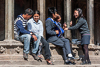 Nepal, Patan.  Young Men and Women Talking in Durbar Square, Sitting on Edge of a Temple.