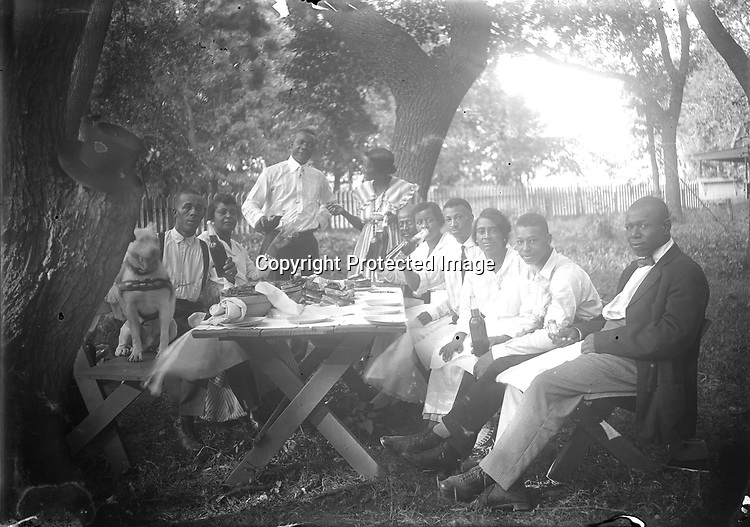 BACKYARD PICNIC. In a backyard enclosed with a picket fence, 10 picnickers (and one pit bull terrier) pause for a toast before their meal. The scene appears casual, but the picnic benches have been angled out from the table to allow each person to be seen, and to lead the eye to the couple serving as host and hostess<br /> <br /> INFORMATION CONTRIBUTED BY STAN SCHMUNK 8/20/2018: The first gent seated on the left is William David Black who owned a home at 708 N. 13 st. He was born in 1876 in Mississippi where his parents had been slaves. In 1908 he married Ella Goodlow in Grand Island, Ne. In 1910 he was shown as a worker in a stone quarry in Weeping Water. By 1920 he owned a little home in Lincoln and was working as a barber. By 1925 his wife was a widow. I found no info on what happened to William. The couple had numerous children. The two young men seated on the right who look like each other and William are Theodore the older and Harry the younger. The widow moved east to live near 24th & Q where she also owned the home. She died in 1937 and is buried in Wyuka. I think she may be the woman seated next to William but can't be sure. At least two of the children ended up in Los Angeles and are buried there. <br /> <br /> <br /> Photographs taken on black and white glass negatives by African American photographer(s) John Johnson and Earl McWilliams from 1910 to 1925 in Lincoln, Nebraska. Douglas Keister has 280 5x7 glass negatives taken by these photographers. Larger scans available on request.