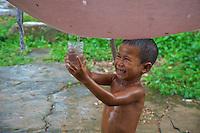 A young boy is collecting rainwater during a monsoon rain shower, Rural area near Battambang, Cambodia